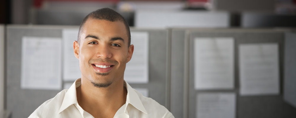 Smiling man standing in an office.